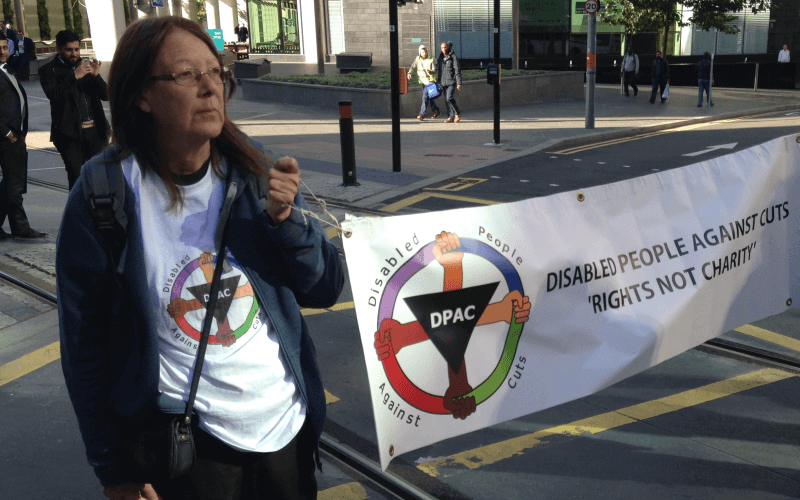 Linda Burnip holding a DPAC banner