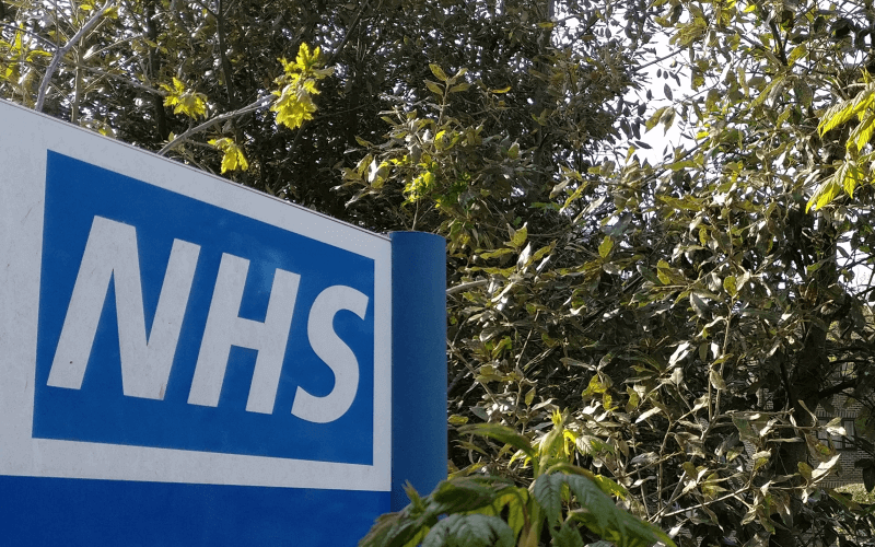 An NHS sign in front of some trees