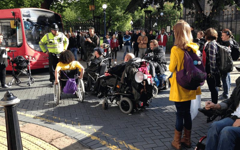 A bus, a police officer and disabled protesters