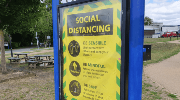 A yellow social distancing sign in a park