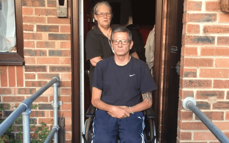 A wheelchair-user and a woman in the doorway to a house