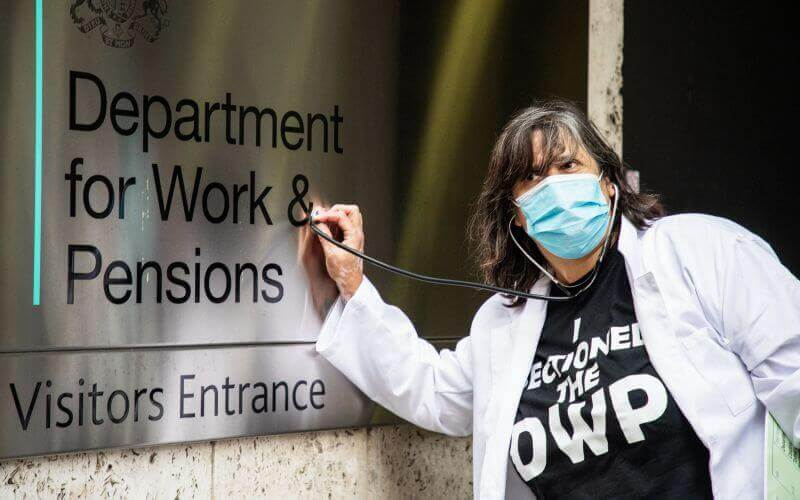 A woman in a face mask and white coat holds a stethoscope against the DWP entrance sign
