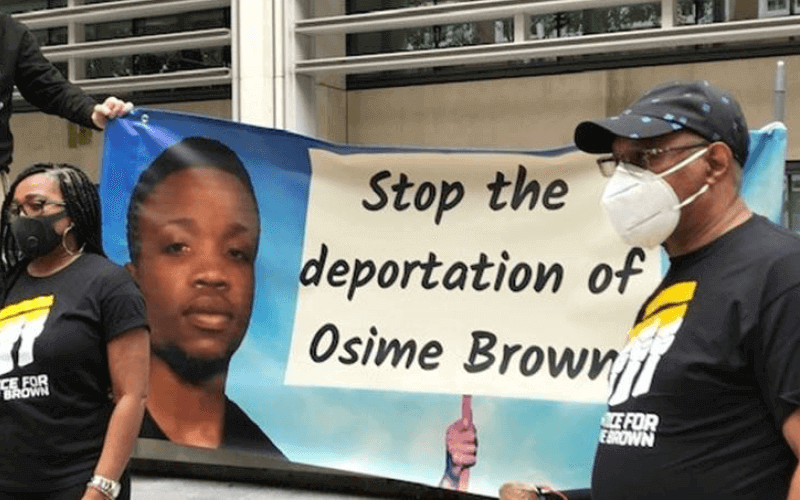 Banner held by a man and a woman, saying: 'Stop the deportation of Osime Brown'