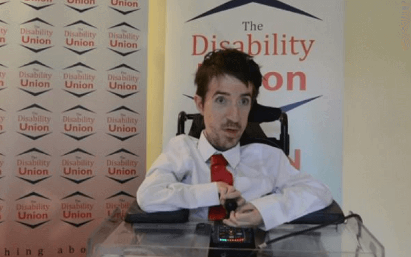 George Baker in front of banners for The Disability Union
