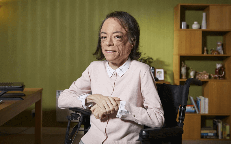 Liz Carr sits in a room in her wheelchair, smiling