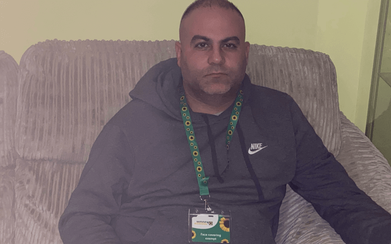 Marco Naayem sitting on a sofa wearing a sunflower lanyard