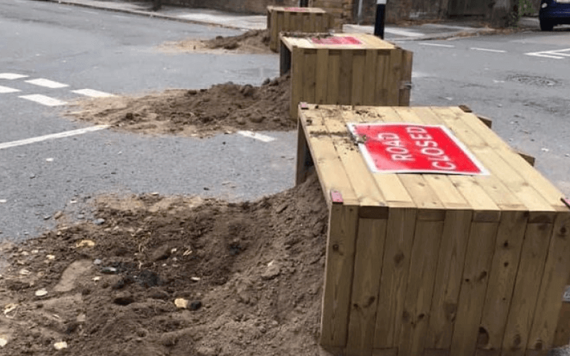 Three overturned planters in a road
