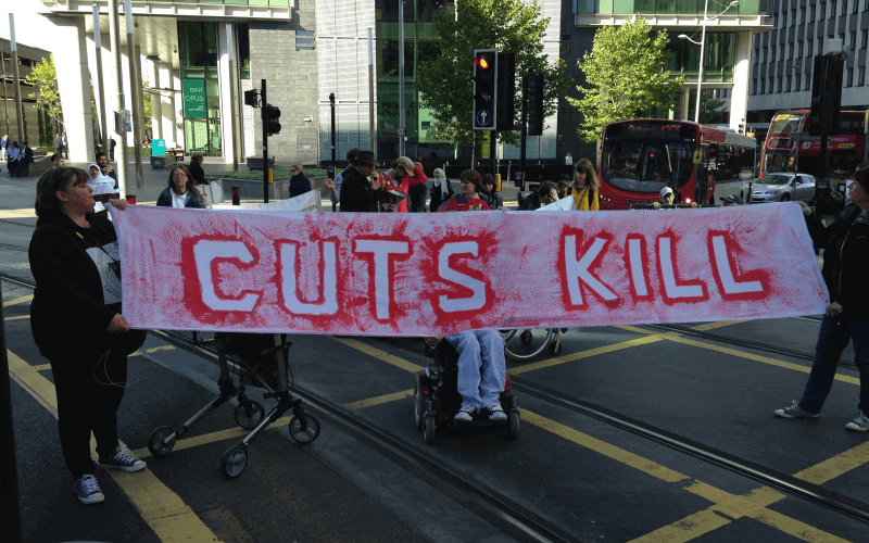 Protesters in a road hold a 'Cuts Kill' banner