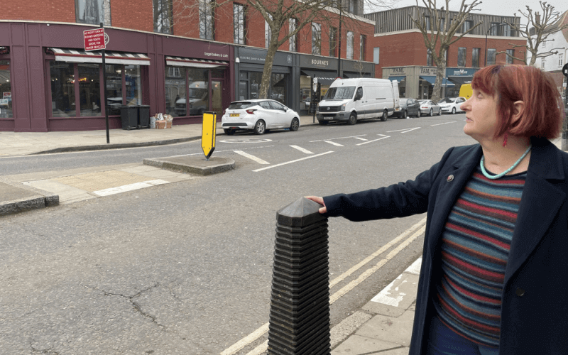 A woman touches a bollard by the side of a road