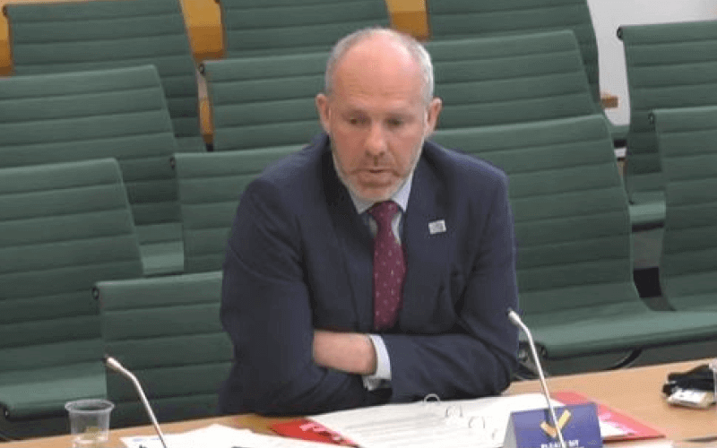 Justin Tomlinson sitting behind a desk in a Commons committee room