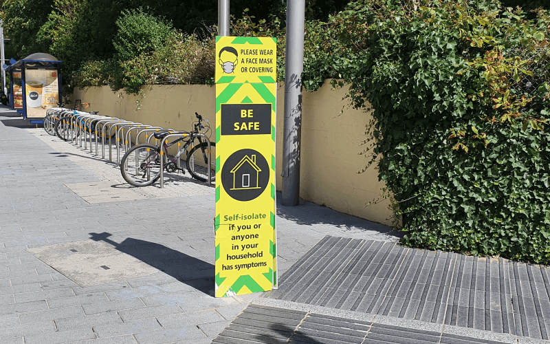 A yellow, green and black COVID warning sign on a pavement