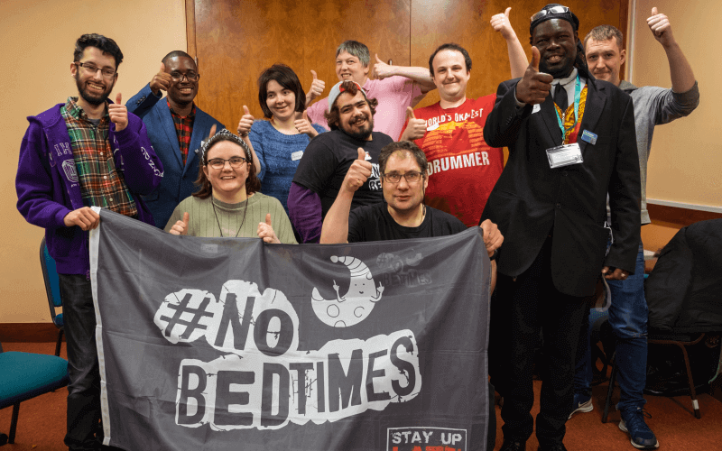 A group of people holding a No Bedtimes banner