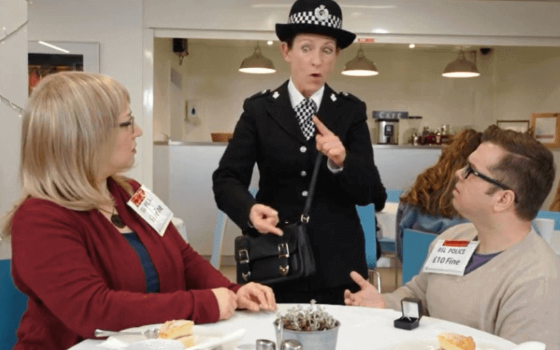 A man and a woman at a cafe table being interviewed by a female police officer