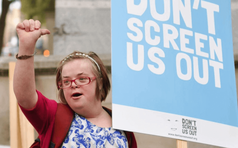 Heidi Crowter raising her fist and holding a Don't Screen Us Out placard
