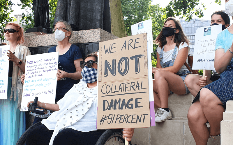 Women in masks holding placards, one says We are not collateral damage