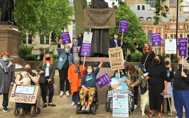 Members of the Women's Equality Party protesting with banners in front of a statue of Millicent Fawcett