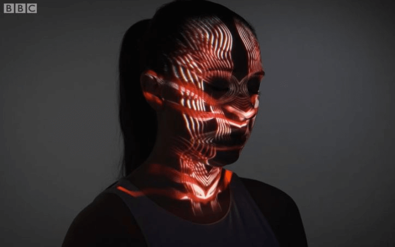 A woman's face with computer-generated images projected onto it