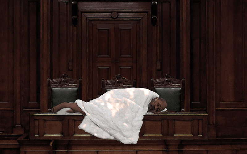 A man lies on a bench in a grand, wood panelled room under a duvet