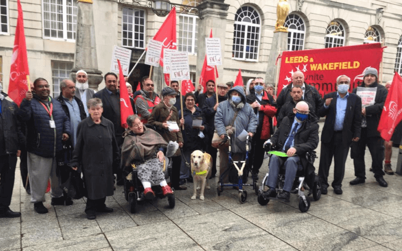 A group of about 20 people, some of them disabled, some holding banners, in front of Leeds Civic Hall