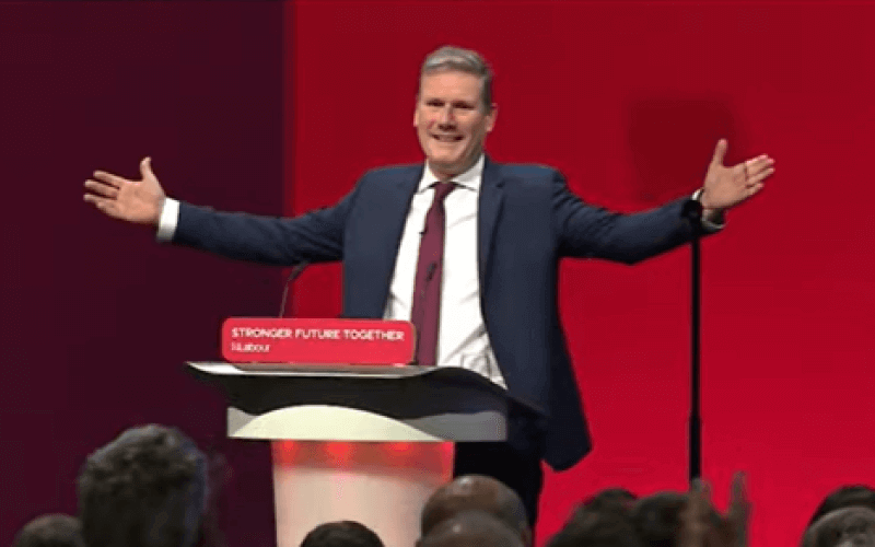 Keir Starmer behind a podium with his arms outstretched