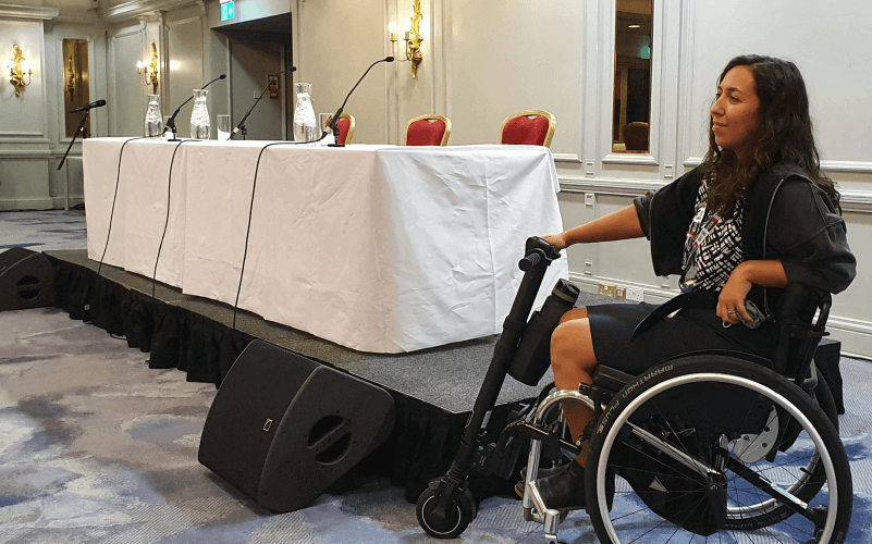 A woman sitting in a wheelchair in front of an inaccessible platform