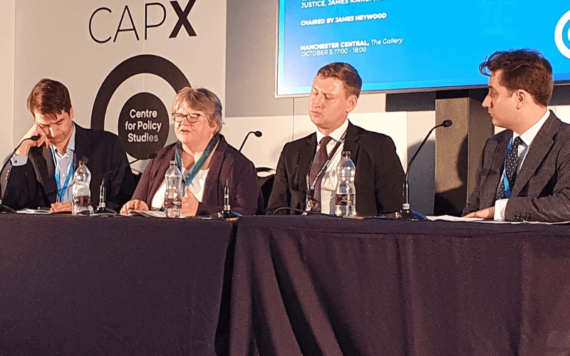 Therese Coffey speaking from behind a long, flanked by three men in suits table