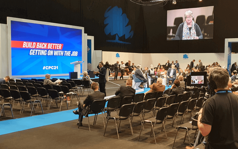 A big screen shows a woman speaking to a half-empty conference hall