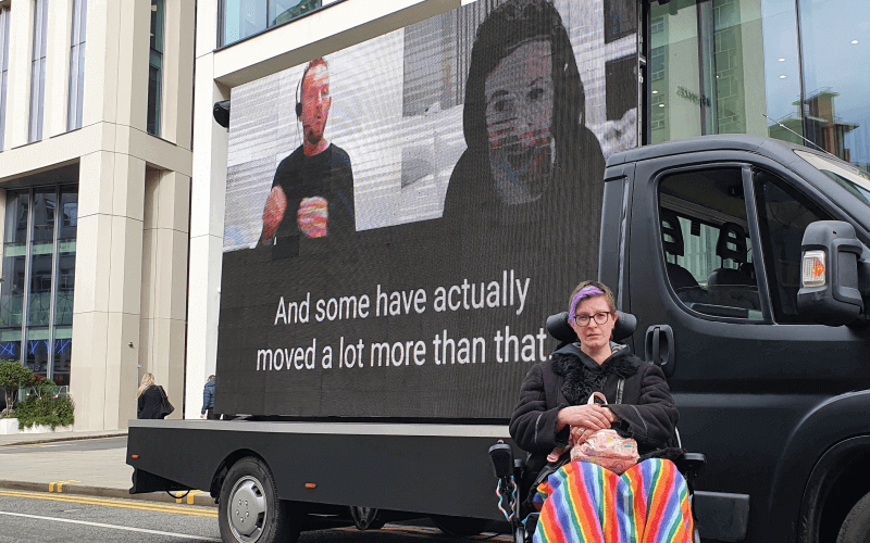 A woman in a wheelchair in front of a van that is carrying a video screen which shows a woman and a BSL interpreter